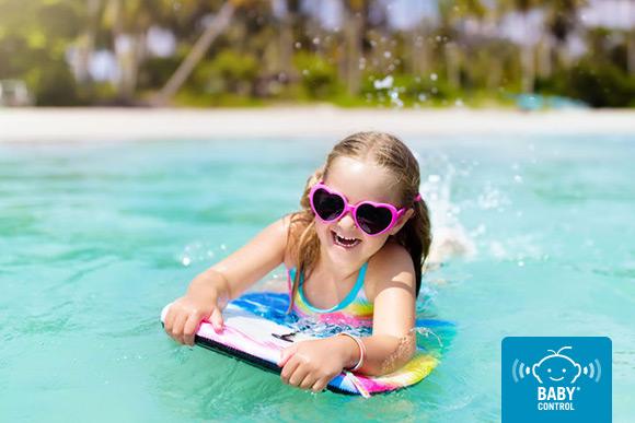 Niña sobre tabla de surf en el mar con gafas de sol