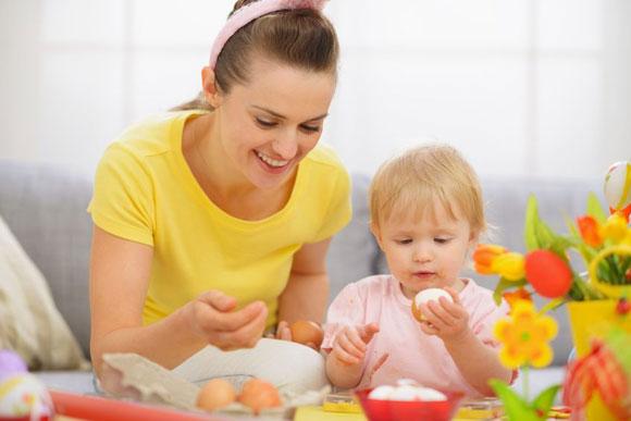 Una madre jugando mientras cocina con su bebé.