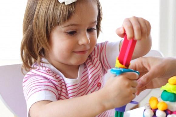 Una niña o alumna jugando con plastilina