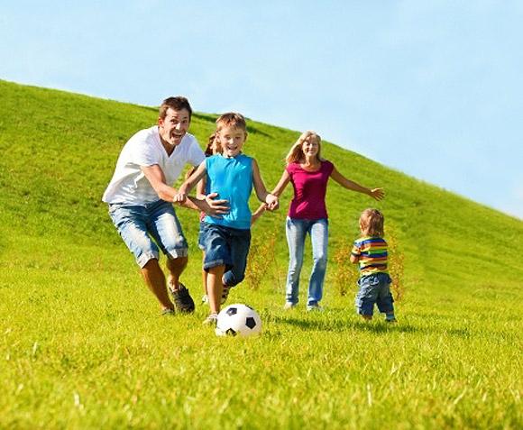 Papas jugando al fútbol con sus hijos en el campo