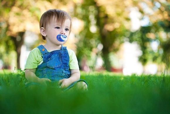 Un niño en el césped con un chupete en la boca