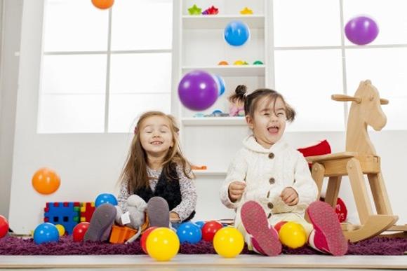 Dos niñas jugando en una habitación llena de juguetes