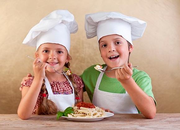 Dos niño con gorros de cocineros comiendo un plato de macarrones