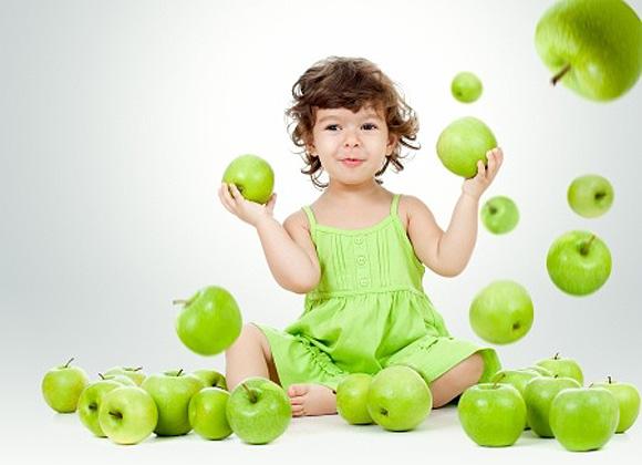 Niña feliz rodeada de manzanas verdes