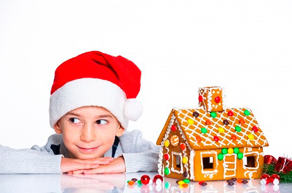 Un niño junto a varios dulces navideños de chocolate