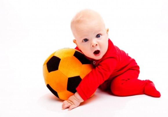 Bebé gateando con una pelota en sus manos
