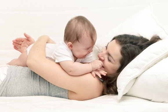 Una mamá con su bebé en un gesto cariñoso