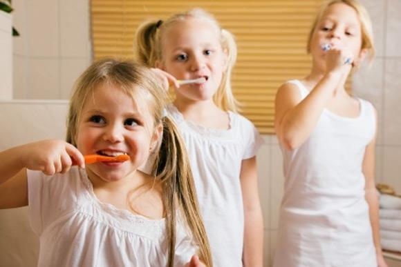 Tres niñas lavándose los dientes