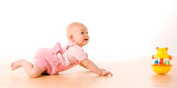 Un bebé gateando intentando alcanzar un juguete