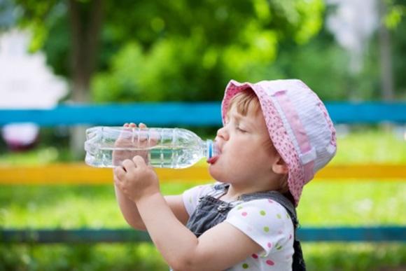 Niño bebiendo agua para prevenir la deshidratación