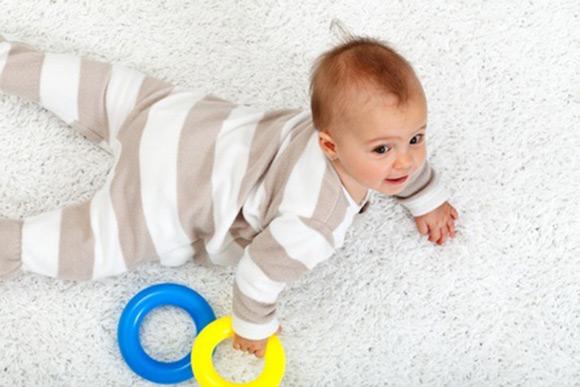 Bebé desplazándose por la alfombra motivado por un juego de estimulación temprana