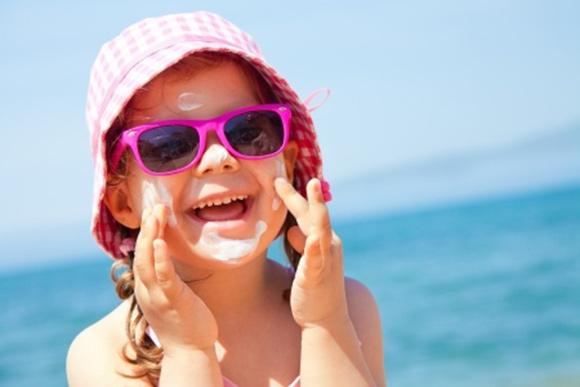 Niña protegiéndose del sol mediante gorro, gafas de sol y crema de protección solar.