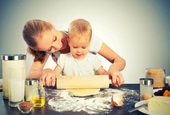 Bebé ayudando a su mamá en la cocina