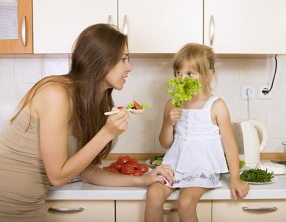 Niña que no quiere comer lo que su mamá le ofrece en una cuchara