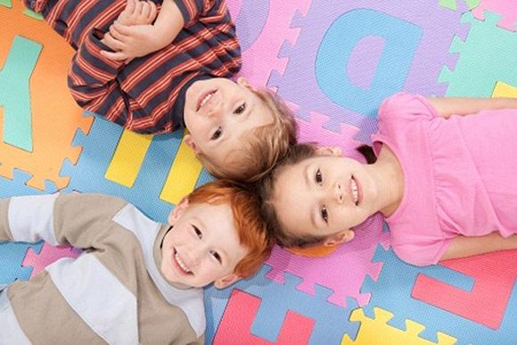Niños que se divierten sobre lona de abecedario en la escuela infantil