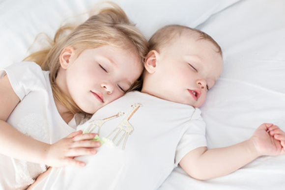 Niña y niño durmiendo la siesta