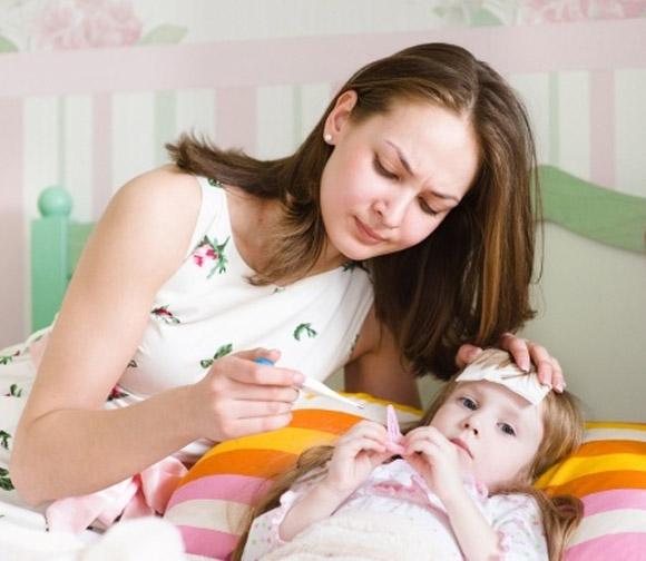 Mamá tomando la temperatura a su hija