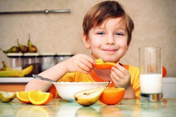 Niño sonriente con desayuno variado de fruta, cereales y lácteos