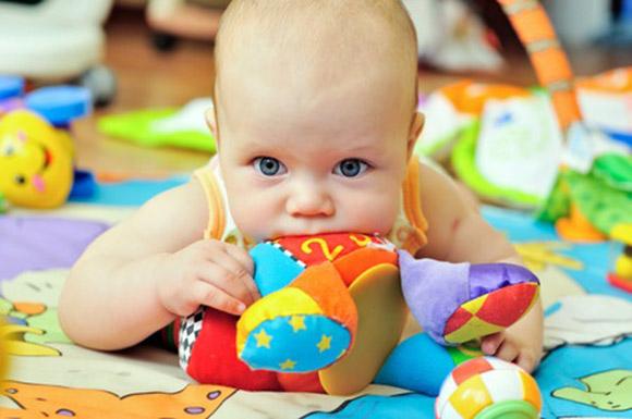 Bebé chupando juguete en el suelo