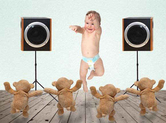 Bebé bailando con música y ositos de peluche