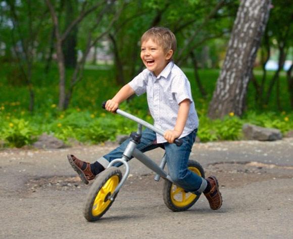 Niño aprendiendo a montar en bicicleta de iniciación (sin pedales)