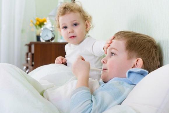 Niña poniendo su mano en la frente de su hermano con gripe en la cama