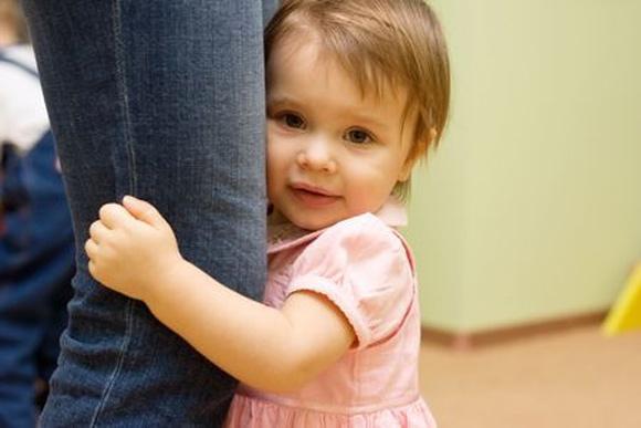 Niña tímida que se enconde detrás de su mamá