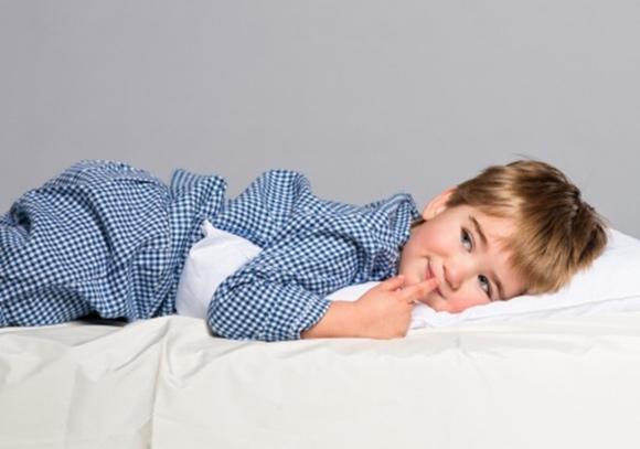 Niño sonriendo tumbado en la cama