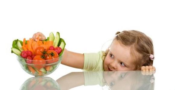 Niña cogiendo un trocito de zanahoria de un bol de picoteo con verduras