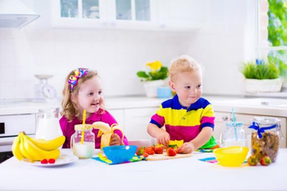 Niños preparando postres con frutas y leche