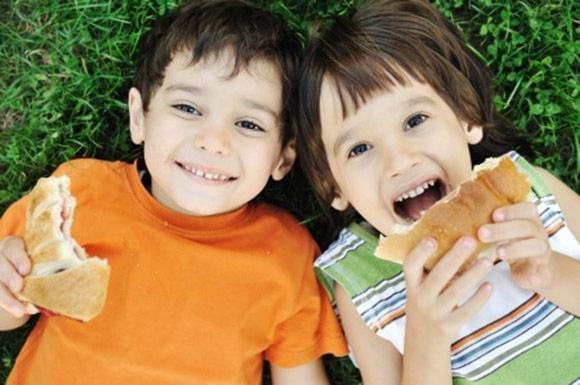 Niños sonrientes comiendo bocadillos