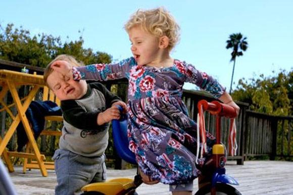 Reacción agresiva de una niña con su hermanito pequeño