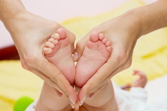 Pies de bebé entre las manos de su mamá