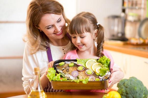 Mamá y su hija con un plato de pescado con muy buena presentación