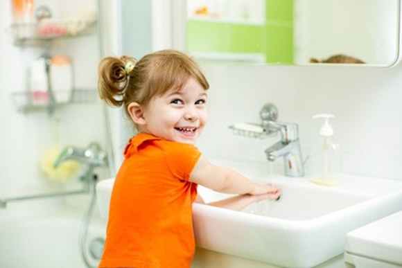 Niña alegre se lava las manos