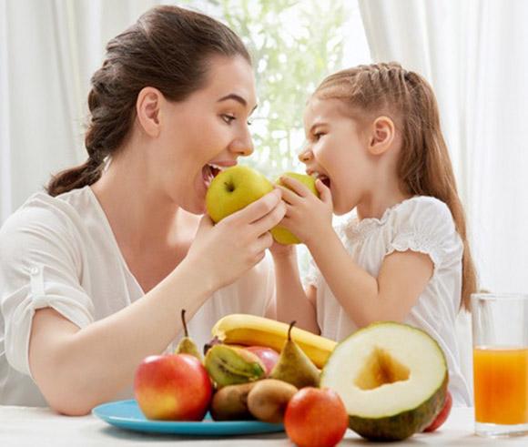 Madre e hija comiendo fruta