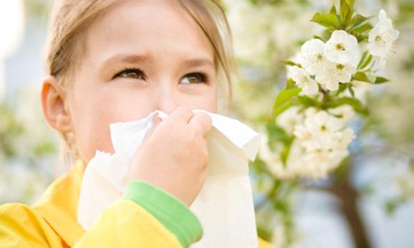 Niña con pañuelo en la nariz rodeada de flores