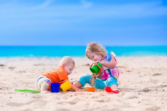 Niiños haciendo castillos de arena en la playa