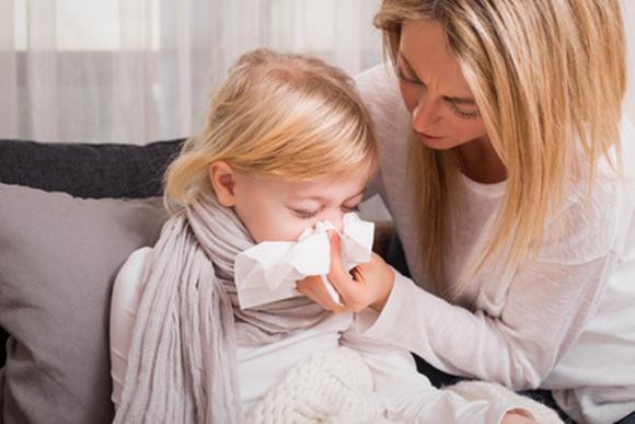 Mamá que enseña a su hija a sonarse la nariz