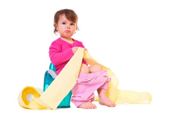 Niña sentada en orinal con rollo de papel higiénico