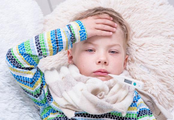Niño con fiebre y termómetro en la boca
