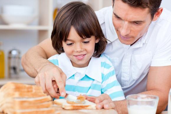 Padre untando crema de frutos secos en pan para su hijo