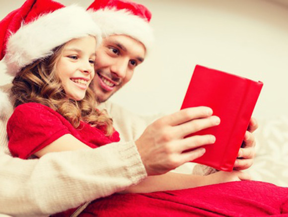 Padre e hija leyendo con gorros navideños