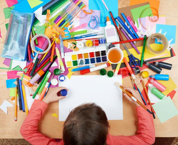 Niños dibujando en una mesa con variados materiales de pintura