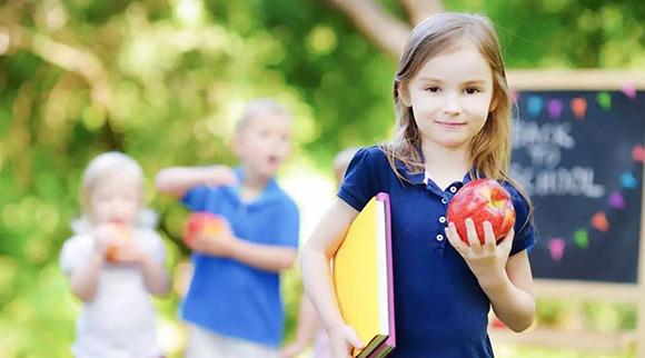 Niñas en la escuela con una manzana