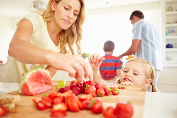 Mamá ofreciendo fruta a su hija