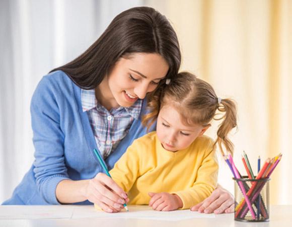 Mamá ayudando a su hija a escribir