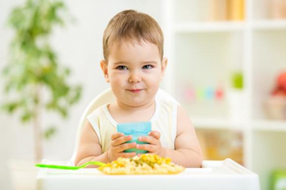 Bebé tomando un plato de pasta con verduras