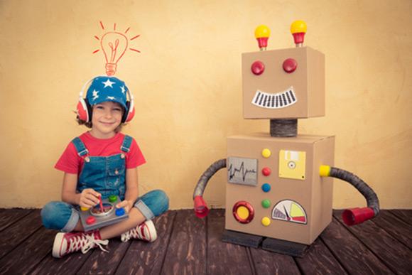 Niño jugando con robot hecho con cajas de cartón