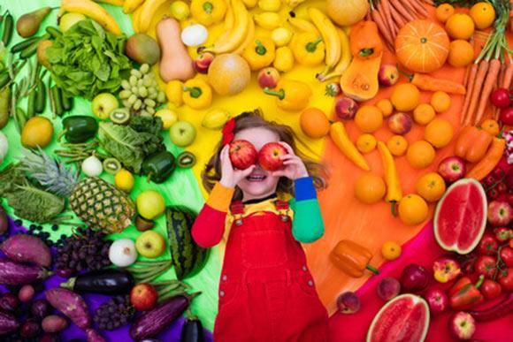 Niña rodeada de frutas y verduras